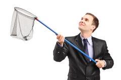 Geschäftsmann, der ein Netz hält Lizenzfreie Stockbilder
