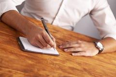 Geschäftsmann, der ein Notizbuch schreibt lizenzfreie stockbilder