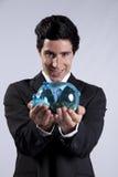Geschäftsmann, der ein piggybank voll von den Münzen anhält Lizenzfreies Stockfoto