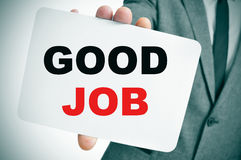 Geschäftsmann, der ein Schild mit dem guten Job des Textes hält Lizenzfreies Stockbild