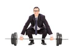 Geschäftsmann, der ein Schwergewicht anhebt Stockfotografie