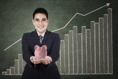 Geschäftsmann, der ein Sparschwein hält Lizenzfreie Stockfotos