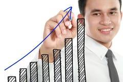 Geschäftsmann, der ein steigendes Diagramm zeichnet Lizenzfreie Stockfotos