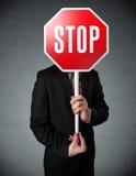 Geschäftsmann, der ein Stoppschild hält Stockbild