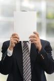 Geschäftsmann, der ein unbelegtes Papier anhält Stockfotos