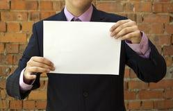 Geschäftsmann, der ein unbelegtes weißes Blatt Papier anhält Lizenzfreie Stockbilder