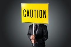 Geschäftsmann, der ein Vorsichtzeichen hält Lizenzfreies Stockfoto
