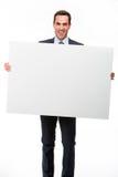 Geschäftsmann, der ein weißes Plakat hält Stockfotos