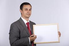 Geschäftsmann, der ein whiteboard anhält Stockfotos