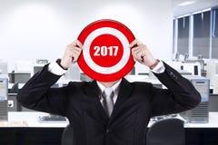 Geschäftsmann, der eine Dartscheibe mit Nr. 2017 hält Lizenzfreies Stockfoto