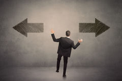 Geschäftsmann, der eine Entscheidung bei der Stellung vor zwei GR trifft Lizenzfreies Stockfoto