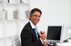 Geschäftsmann, der eine Frucht bei der Arbeit isst Lizenzfreie Stockbilder