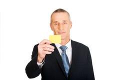 Geschäftsmann, der eine gelbe Identitätsnamenkarte zeigt Stockfotos