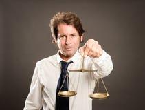 Geschäftsmann, der eine Gerechtigkeitsskala hält stockbilder