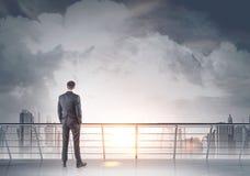 Geschäftsmann, der eine graue Stadt von einem Balkon betrachtet Stockfoto