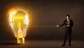 Geschäftsmann, der eine große helle glühende Glühlampe zieht Stockfotos