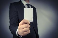 Geschäftsmann, der eine leere Goldvisitenkarte in seiner Hand hält Stockfotos