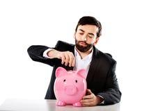 Geschäftsmann, der eine Münze zum piggybank setzt Lizenzfreie Stockfotos
