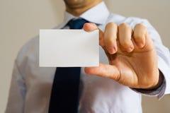 Geschäftsmann, der eine Namenskarte anhält Stockbilder