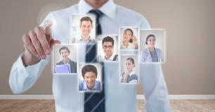 Geschäftsmann, der eine Person von der Gruppe von Personenen-Schnittstelle aufeinander einwirkt und wählt stockfoto