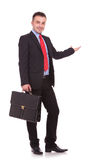 Geschäftsmann, der eine schwarze Aktentasche beim Darstellen hält Stockbild