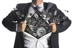 Geschäftsmann, der eine Superheldklage unter Maschinerie zeigt Lizenzfreie Stockfotos