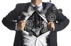 Geschäftsmann, der eine Superheldklage unter Maschinerie zeigt Stockfotografie