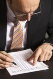 Geschäftsmann, der eine Tabelle studiert Lizenzfreie Stockfotografie