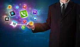 Geschäftsmann, der eine Tablette mit modernen bunten apps und Ikonen hält Lizenzfreie Stockbilder