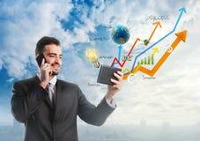 Geschäftsmann, der eine Tablette mit wachsenden Grafiken hält Lizenzfreies Stockfoto
