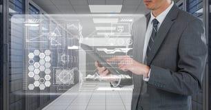 Geschäftsmann, der eine Tablette und Grafiken im Serverraum hält Lizenzfreies Stockbild
