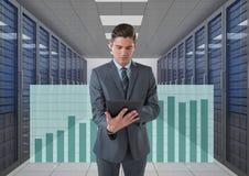 Geschäftsmann, der eine Tablette und Grafiken im Serverraum hält Lizenzfreie Stockfotografie