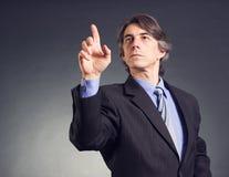 Geschäftsmann, der eine Taste bedrängt Lizenzfreie Stockbilder
