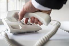 Geschäftsmann, der eine Telefonnummer wählt Stockfotografie