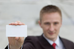 Geschäftsmann, der eine unbelegte Visitenkarte übergibt Stockfotografie