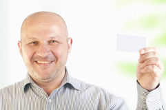 Geschäftsmann, der eine unbelegte Visitenkarte anhält Stockfotografie