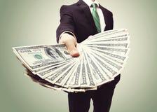 Geschäftsmann, der eine Verbreitung des Bargeldes anzeigt stockfotografie