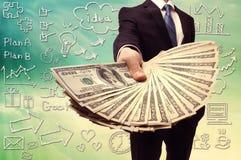 Geschäftsmann, der eine Verbreitung des Bargeldes anzeigt Stockbilder