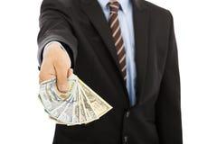Geschäftsmann, der eine Verbreitung von US-Dollar Bargeld anzeigt Lizenzfreie Stockbilder