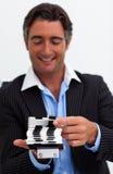 Geschäftsmann, der eine Visitenkartehalterung konsultiert Stockfotografie