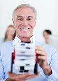 Geschäftsmann, der eine Visitenkartehalterung konsultiert Lizenzfreie Stockfotos