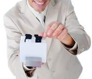 Geschäftsmann, der eine Visitenkartehalterung konsultiert Lizenzfreie Stockbilder