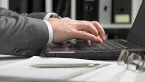 Geschäftsmann, der in einem Büro arbeitet und einen Laptop verwendet Finanzbuchhaltungskonzept des Geschäfts stock footage