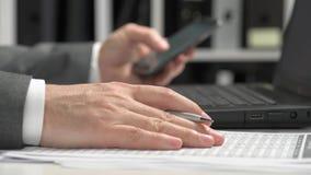 Geschäftsmann, der in einem Büro arbeitet und Smartphone und Laptop verwendet Finanzbuchhaltungskonzept des Gesch?fts stock video