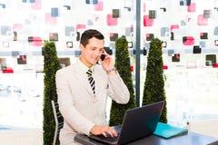 Geschäftsmann, der in einem Café sitzt Stockbilder
