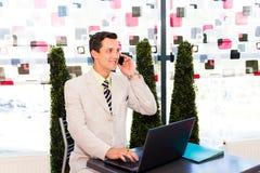 Geschäftsmann, der in einem Café sitzt Lizenzfreies Stockfoto
