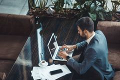 Geschäftsmann, der in einem Geschäftszentrumrestaurant schreibt auf Draufsicht des Laptops sitzt lizenzfreie stockfotos