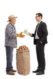 Geschäftsmann, der einem Landwirt Geld gibt stockfotografie