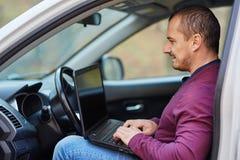 Geschäftsmann, der an einem Laptop im Auto arbeitet Lizenzfreie Stockfotografie
