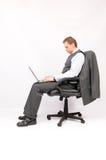 Geschäftsmann, der in einem Lehnsessel mit einem Laptop sitzt. Lizenzfreie Stockfotos